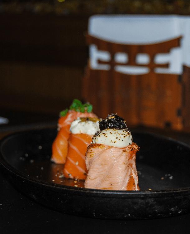 Três sushis de Joe Salmão em prato preto sobre uma mesa de madeira com fundo desfocado